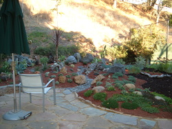 Slate rock patio and walkway as part of backyard landscape.