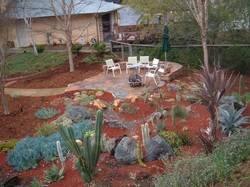 Rock patio amid water-wise xeriscape.